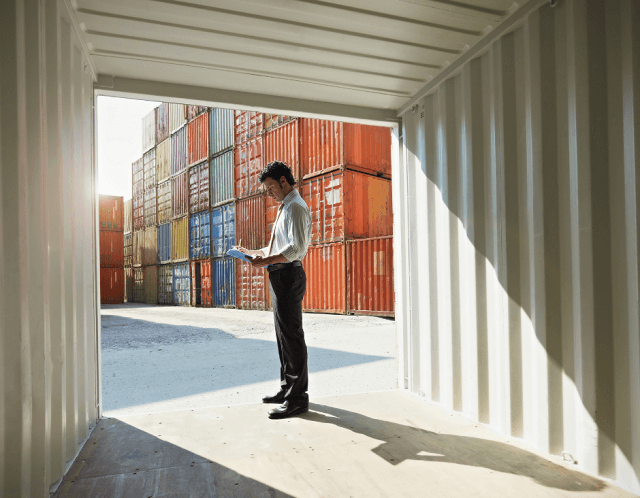 man standing at port terminal with containers