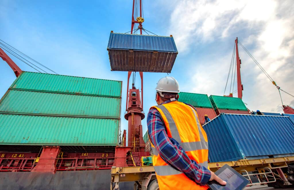 shipping containers being handled at port terminal